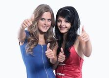 Un primo piano di due ragazze che mostrano i loro pollici su contro Immagini Stock