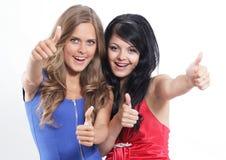 Un primo piano di due ragazze che mostrano i loro pollici su contro Fotografie Stock