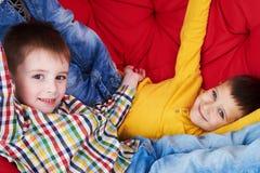 Un primo piano di due ragazzi che si rilassano su uno strato rosso molle, wh pigro di menzogne Fotografia Stock Libera da Diritti
