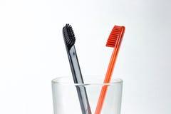 Un primo piano di due spazzolini da denti in un becher di vetro Per gli uomini e le donne Immagini Stock