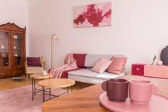 Un primo piano di due tazze di caffè sulla tavola in salone elegante con lo strato grigio con i cuscini rosa pastelli, poltrona a fotografia stock libera da diritti