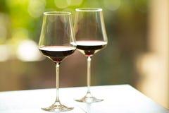 Un primo piano di due vetri del vino rosso con un'atmosfera variopinta e soleggiata Immagini Stock