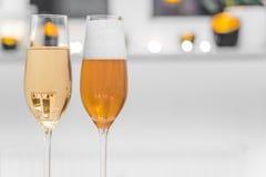 Un primo piano di due vetri ha riempito di champagne e di birra Fotografie Stock