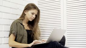 Un primo piano di giovane studentessa di modello graziosa sta funzionando con il computer portatile che si siede sul pavimento Fotografia Stock Libera da Diritti