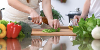 Un primo piano di quattro mani umane sta cucinando in una cucina Amici divertendosi mentre preparando insalata fresca vegetariano fotografie stock