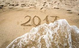 Un primo piano di 2017 scritto sulla sabbia che è rimossa dall'onda Immagini Stock