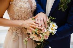 Un primo piano di un telaio potato della sposa e dello sposo che stanno parallelamente e che toccano il loro mazzo di nozze, most immagini stock libere da diritti