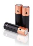 Un primo piano di tre batterie di aa su bianco Fotografia Stock