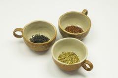 Un primo piano di tre ciotole marroni dell'argilla con le foglie di tè immagini stock libere da diritti