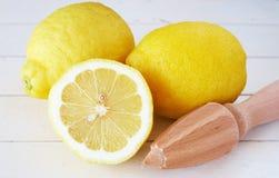 Un primo piano di tre limoni e juicer del limone su bianco immagini stock libere da diritti