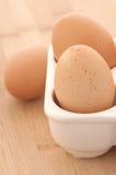 Un primo piano di tre uova di Brown in una scatola su legno Fotografie Stock