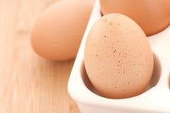Un primo piano di tre uova di Brown in una scatola su legno Fotografia Stock