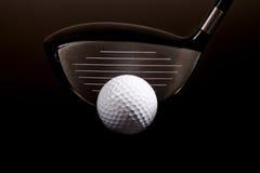 Un primo piano di un driver di golf e di una sfera di golf sul nero Fotografia Stock
