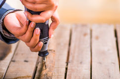 Un primo piano di un uomo del hardworker che perfora un bastone di legno con il suo trapano su un fondo di legno Fotografia Stock