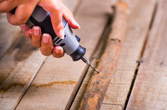 Un primo piano di un uomo del hardworker che perfora un bastone di legno con il suo trapano su un fondo di legno Immagine Stock Libera da Diritti