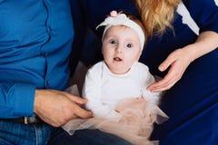 Un primo piano di una bambina sta guardando intento nei vostri occhi Il bambino si siede fra i suoi genitori Le mani della madre immagini stock