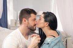 Un primo piano di una coppia felice che abbraccia e che bacia nella camera da letto fotografia stock libera da diritti