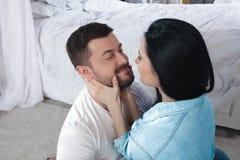Un primo piano di una coppia felice che abbraccia e che bacia nella camera da letto immagine stock