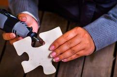Un primo piano di una donna del hardworker che per mezzo di un lucidatore sopra un pezzo grigio di puzzle su un fondo di legno Fotografia Stock Libera da Diritti