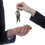 Un primo piano di una mano con i portachiavi a anello consegna le chiavi all'altra mano Immagine Stock