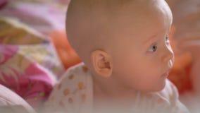Un primo piano di una neonata sveglia su biancheria da letto variopinta archivi video