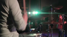 Un primo piano di un uomo che gioca lo strumento di percussione mentre l'altro uomo sta cantando in scena illuminazione di concer video d archivio