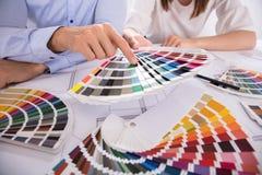 Un primo piano due dell'architetto Holding Colorful Swatch sopra il modello fotografia stock