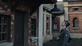 Un primo piano posteriore di un soldato tedesco che cambia una lampadina in una lampada di via che appende sopra una porta in un  stock footage