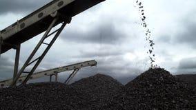 Un primo piano sparato dei bei pezzi del carbone che cadono dai nastri trasportatori alla miniera di carbone archivi video