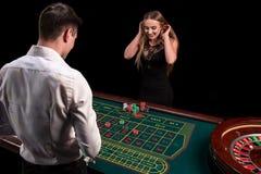 Un primo piano sul retro del croupier in una camicia bianca, immagine della tavola verde del casinò con le roulette e chip, ricch fotografie stock