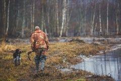 Un processo di caccia durante la stagione di caccia, processo di caccia dell'anatra, gruppo di cacciatori e cane wirehaired drath Immagini Stock