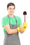 Un producto de limpieza de discos masculino sonriente que sostiene una escoba del retrete Imagen de archivo libre de regalías
