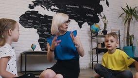 Un profesor en una lección enseña con sus alumnos las estaciones del año en la clase geográfica Lección de la geografía almacen de video
