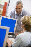 Un profesor habla con un colegial que usa un ordenador Fotos de archivo libres de regalías