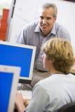 Un profesor habla con un colegial que usa un ordenador Imágenes de archivo libres de regalías