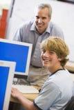 Un profesor habla con un colegial que usa un ordenador Imagen de archivo