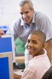 Un profesor habla con un colegial que usa un ordenador Imagen de archivo libre de regalías