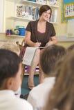 Un profesor que se sienta con los alumnos primarios Imagen de archivo