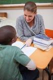Un profesor sonriente que explica algo a una pupila Imágenes de archivo libres de regalías