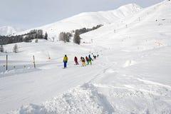 Un professeur et enfants de ski apprenant le ski dans la piste de ski dans les alpes Suisse Photos stock