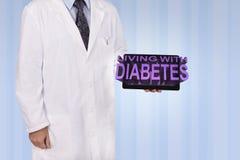 Un professionnel médical tient un comprimé montrant les mots Livin Image stock