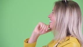 Un profilo di chiusura di un pensiero di una giovane donna bionda felice e ribelle stock footage