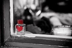 Un profumo del giorno di biglietti di S. Valentino imbottiglia una finestra di deposito Fotografia Stock