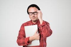 Un programador joven en un sombrero negro está sosteniendo un ordenador portátil en sus manos fotografía de archivo