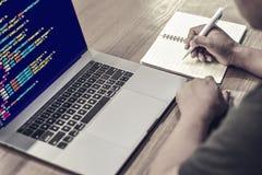 Un programador que escribe notas en un cuaderno con los códigos fuente programados que exhiben en la pantalla de un ordenador por imágenes de archivo libres de regalías