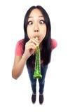 Un projectile grand-angulaire d'une fille asiatique soufflant un bruit Image libre de droits
