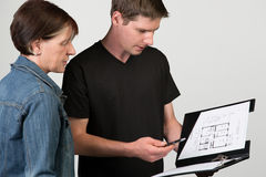 Un proprietario spiega un floorplan ad un cliente femminile, isolato sopra Fotografia Stock Libera da Diritti