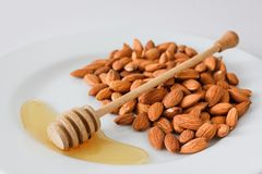 Un puñado de almendras en una placa con la miel y la cuchara de la miel en un fondo blanco imagen de archivo