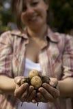 Un puñado sonriente de la explotación agrícola de la mujer de patatas Imagenes de archivo