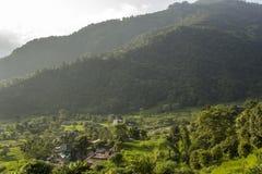 Un pueblo contiene en terrazas verdes claras del arroz de campos en la ladera contra la perspectiva de las montañas enselvadas fotos de archivo